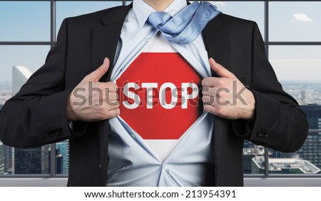 A concept of preventing risks. Businessman tears the shirt with the stop sign on the chest. - stock photo