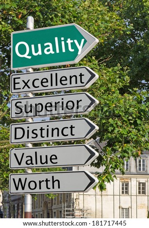 A concept road sign pointing in the direction of 'Quality' with some descriptive words underneath - stock photo
