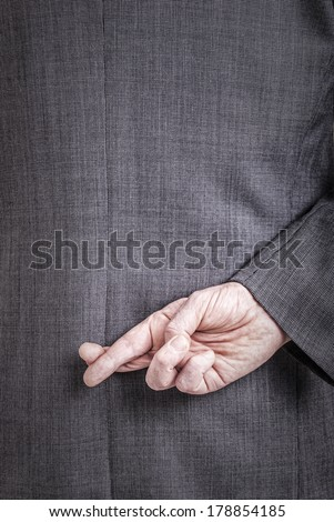 A conceptial image of a business man with his fingers crossed behind his back. - stock photo
