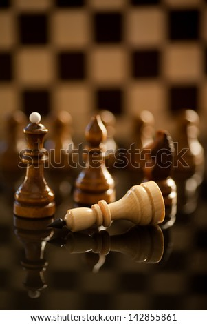 A conceptual composition of chess pieces standing over defeated king on reflective surface