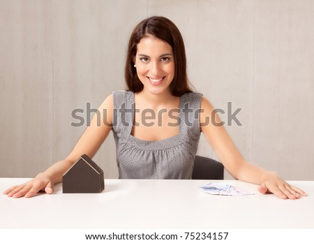 A conceptual housing market shot, a woman with model house and Euro money - stock photo