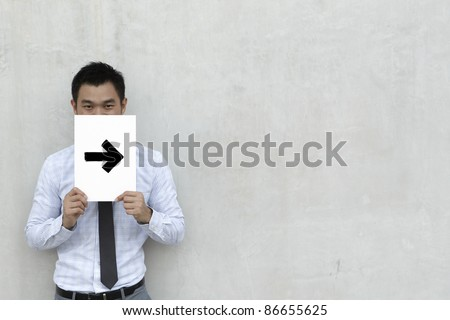 A conceptual image about direction. The Asian Business man is holding an arrow sign. - stock photo