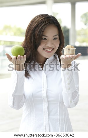A conceptual image about food choice. The Asian woman holding an apple and a cake. - stock photo