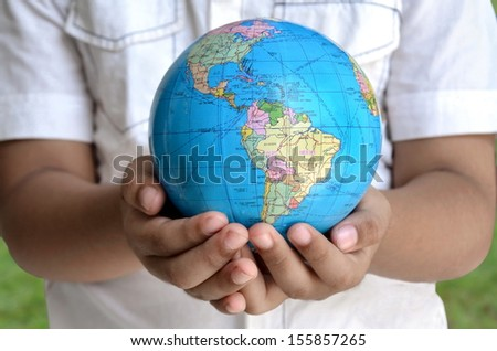 A conceptual image of a boy holding the earth globe with his two hand. A symbol of hope, future generation and  saving the planet for future generation. - stock photo