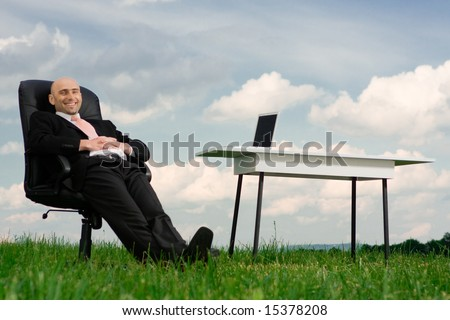 A conceptual image of a businessman without office space relaxing on his chair with his desk in the outdoors.