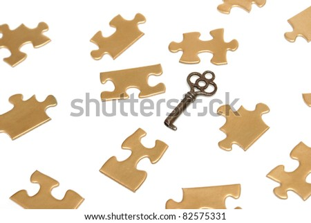 A conceptual image of golden puzzle pieces and an old skeleton key. - stock photo