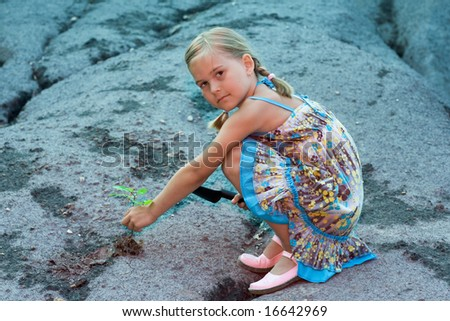 A conceptual picture of little girl planting a tree on a rocky surface. - stock photo