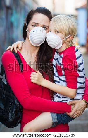 A concerned woman and her son wearing protective face masks for pollution or virus. - stock photo