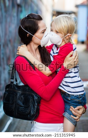 A concerned woman carrying her son. Both are wearing protective face masks for pollution or virus. - stock photo
