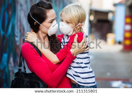 A concerned woman looking at her sick son. Both are wearing protective face masks for pollution or virus. - stock photo