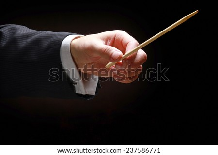 A concert conductor's hands with a baton, isolated on a black background