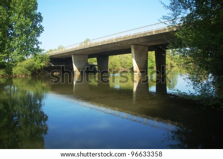 A concrete bridge passing over the river Sarthe in France. - stock photo