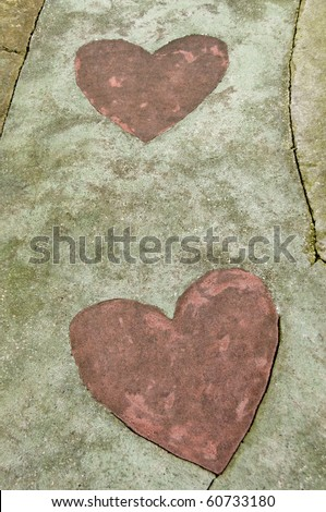 A concrete path with two hearts on it. - stock photo
