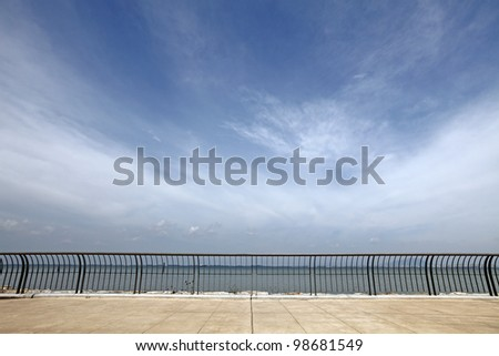 A concrete platform with metal railings overlooking a coastal seafront with dramatic swirling cloud on a blue sky. - stock photo