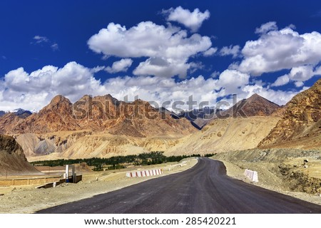 A concrete road towards beautiful rocky mountains and blue sky with peaks of Himalaya, Leh, Ladakh, Jammu and Kashmir, India - stock photo
