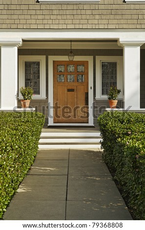A concrete walkway bordered with hedged shrubs leads to the front door of a home. There are windows on either side of the door. Vertical shot. - stock photo