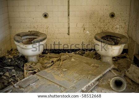 A condemned bathroom with dirty toilets in an abandoned building.
