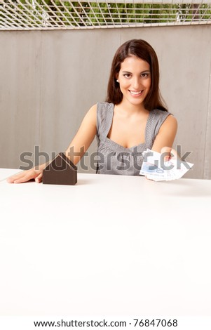 A coneptual shot with a woman offering euro money and a model house - stock photo