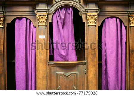 A confessional with purple curtains in a church in Prague.