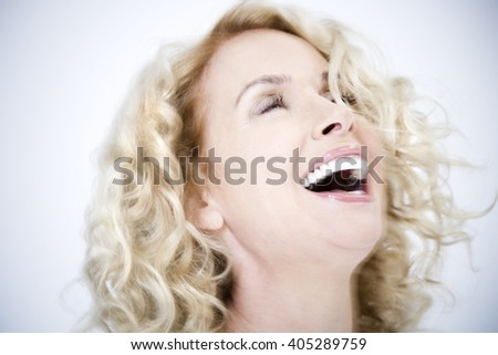 A confident and attractive middle-aged woman in white, laughing - stock photo