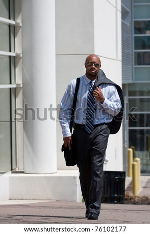 A confident business man carries his suit jacket over his shoulder while walking down the sidewalk in the city. - stock photo
