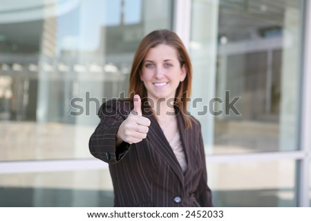 A confident business woman with her thumb up - stock photo