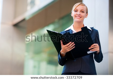 A confident businesswoman holding a clipboard outside her office in the city
