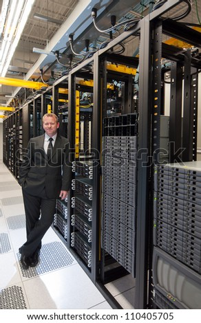 A confident datacenter manager posing by a large scale storage system with a smile.