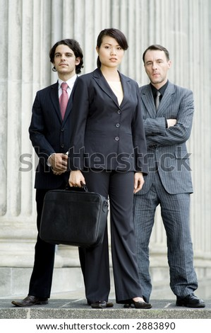 A confident looking business team standing outside