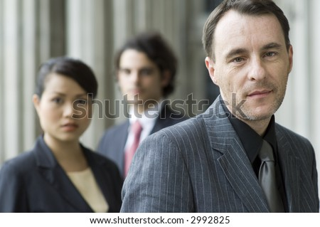 A confident looking businessman standing in front of his team (shallow depth of field used)