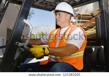 A confident male industrial worker driving forklift at workplace