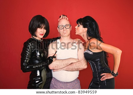 A confident man is surrounded by two playful dominatrix women.