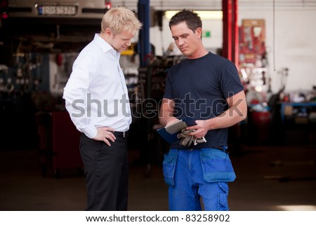 A confident mechanic showing work report to business man