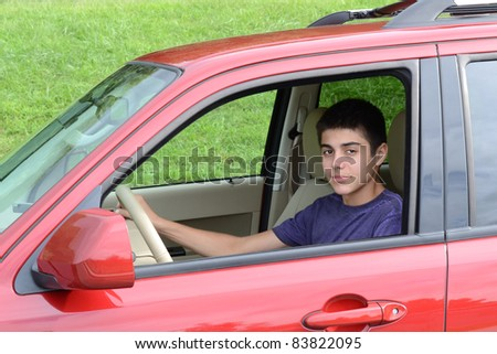 A confident newly licensed teenage male driver sits in his shiny new red car. Close up in horizontal format showing the young caucasian man as he sits behind the wheel. - stock photo