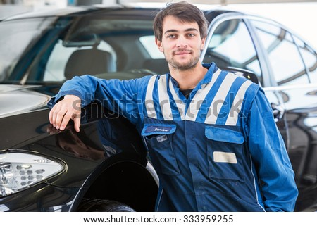 A confident, reliable, trustworthy looking professional mechanic, leaning against a black sedan - stock photo
