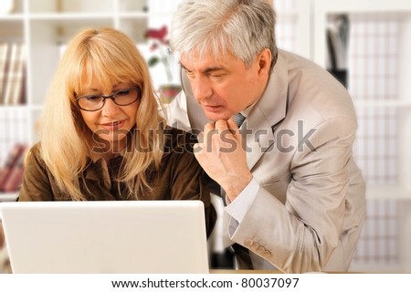 A confident smiling business woman with her colleague at modern comfortable office working using laptop - stock photo