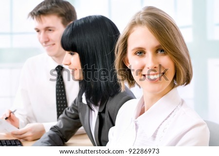 A confident young business woman smiling with her colleagues at the back - stock photo