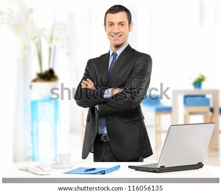 A confident young businessman posing in his office - stock photo