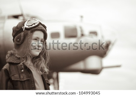 A confident young female pilot is gazing into the distance, wearing flight jacket / hat / goggles.  Bomber is visible in the background out of focus. - stock photo