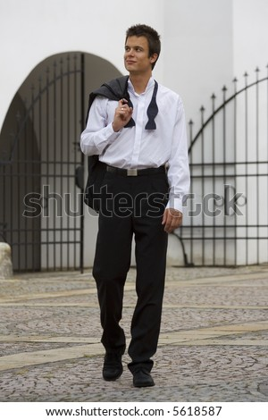 A confident young man coming home in the morning still dressed in the black tie outfit from the night out before - stock photo