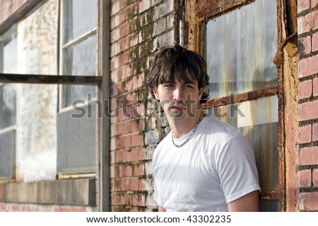 A confident young model standing in a grungy urban setting.
