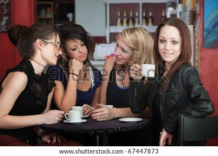 A confident young woman drinks coffee with friends in a cafe