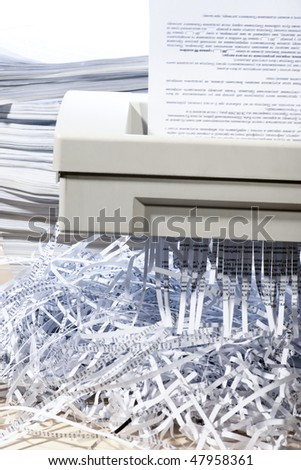A confidential document being put through a shredder - stock photo