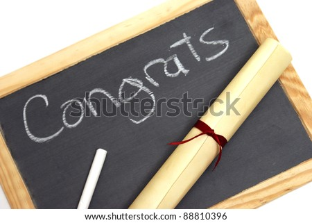 A congratulation note wrote in chalk with a diploma. - stock photo