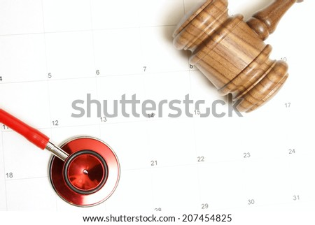 A connection of two forces of medicine and law on top of a calendar. - stock photo