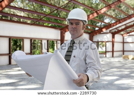 A construction engineer reviewing blueprints on the job. - stock photo