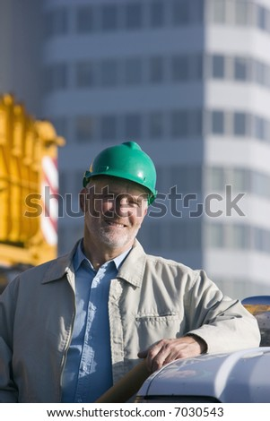 A construction engineer standing leaning on the hood of his truck - stock photo