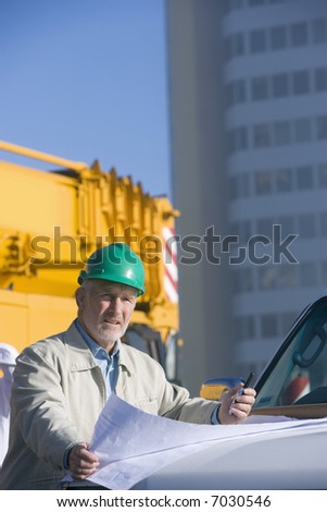 A construction engineer standing leaning on the hood of his truck, and studying plans - stock photo