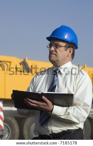 A construction engineer taking notes with a large vehicle behind him - stock photo