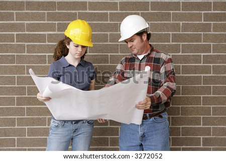 A construction foreman going over blueprints with a female apprentice. - stock photo